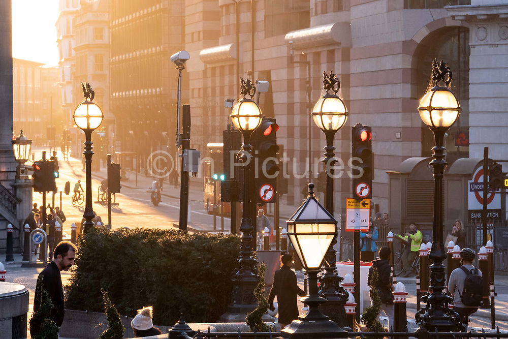 Evening sunlight illuminates the Bank Triangle junction during a much quieter evening rush-hour during the third lockdown of the Coronavirus pandemic. Financial institutions and the Bank of England are located here, in the heart of the City of London, aka Square Mile, on 27th February 2021, in London, England.