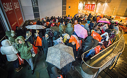 © Licensed to London News Pictures . 26/12/2014 .  Manchester , UK . Crowds of bargain hunters queue in the rain outside Next in Manchester's Arndale Centre from midnight , for a 6AM opening for the Boxing Day Sale . Photo credit : Joel Goodman/LNP