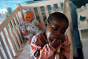 Nonceba, 3, a HIV+ girl, is tanding in her bed at Thembacare HIV+ children's care hospice in Athlone, Cape Town.