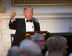 United States President Donald J. Trump shares a toast during the State Dinner for President Emmanuel Macron and Mrs. Brigitte Macron of France during a visit to The White House in Washington, DC, April 24, 2018. Credit: Chris Kleponis / Pool via CNP