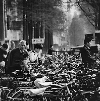 A older man and child amongst a mass of bikes in front of a Wuhan department store, China.