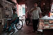 """Doña Inés Abregó (50) junto a su hijo Ismael (18) detrás Don Lucho Moreta (64) su esposo y padre de sus 5 hijos. Sus dos hijos varones atravesaron un cuadro de parálisis motor neurodegenerativo (sin diagnosticar) durante 8 años y ambos fallecieron a los 15. Ismael fue el tercer hijo varón. Era apenas un bebé cuando fallecieron sus hermanos. Actualmente tiene 18 años y también comenzó a perder fuerza muscular a sus 9 años. """"Es terrible. Porque él sabe lo que pasó con sus hermanos"""" Dice Doña Inés. Esta familia nunca fue incluida dentro de las pensiones por discapacidad. A pesar del exceso de informes que Doña Inés presenta ante los organismos estatales cada vez que puede viajar más de tres horas y subir a Ismael a un ómnibus público sin rampa. Completamente inaccesible. Don lucho no puede acompañarlos porque está perdiendo la vista por un cuadro de diabetes. Doña Inés es quien se encarga de cuidar de toda la familia al punto de olvidarse de ella misma."""