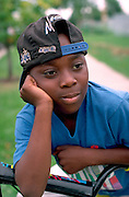 Youth age 10 resting thoughtfully on bicycle.  St Paul  Minnesota USA