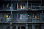 A man visits with a neighbor as another peers out the window in an apartment complex in Kargil