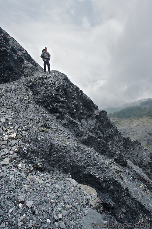 A hiker in Taiwan crosses a giant landlide caused by Typhoon Morkot in 2009.