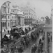 Second Boer War 1899-1900: South African Light Horse proceeding along Adderly Street, Cape Town, to entrain for the front 1900. British Colonialism Soldier Mounted City Traffic Transport Cart Electric Tram