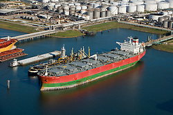 Aerial view of docked oil tankers and barges at the Port of Houston with tank farm in the background.