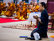 25 OCTOBER 2017 - BANGKOK, THAILAND: A man kneeling in front of monks prays during the funeral for Bhumibol Adulyadej, the Late King of Thailand. He died in October 2016 and was cremated during an ornate five day funeral on 26 October 2017. He reigned for 70 years and was Thailand's longest serving monarch.         PHOTO BY JACK KURTZ