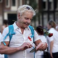 Nederland, Amsterdam , 23 juli 2014.<br /> Duizenden mensen lopen mee met een stille tocht door het centrum van Amsterdam. Volgens de organisatie zijn er zo'n vijfduizend deelnemers, meldt persbureau Novum. De wandeling begon om 20.00 uur op de Dam en eindigt daar ook weer. Deelnemers zullen daar witte ballonnen oplaten. Ook dragen zij witte kleding.<br /> Thousands of people in white clothes walk along with a silent march through the center of Amsterdam. The victims of flight MH17 are thus commemorated. National day of Mourning .