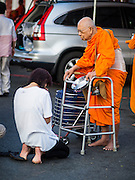 31 MARCH 2015 - BANGKOK, THAILAND: An elderly Buddhist monk with a walker receives alms from Thai Buddhists at Wat Benchamabophit. Wat Benchamabophit Dusitvanaram, a Buddhist temple (wat) in the Dusit district of Bangkok, Thailand. Also known as the marble temple, it is one of Bangkok's best known temples and a major tourist attraction. It typifies Bangkok's ornate style of high gables, stepped-out roofs and elaborate finials. Monastic life at Wat Bencha differs from most other temples in that lay people come to the temple to present food and alms to the monks rather than the monks going out and walking through the community as they do at most other Thai temples.     PHOTO BY JACK KURTZ