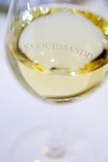 A glass of white burgundy wine engraved with Le Gourmandin against a white background linen table clot in the restaurant Le Gourmandin in Beaune Cote d'Or Burgundy Bourgogne France Europe