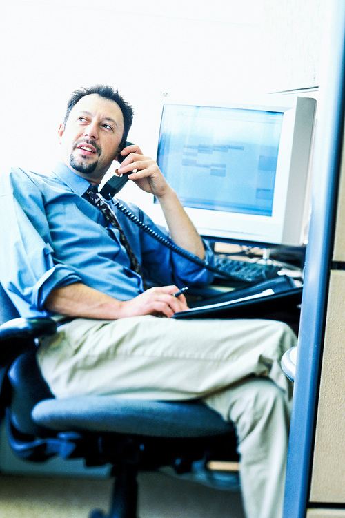 1990's businessman in an office cubicle talking on the phone.