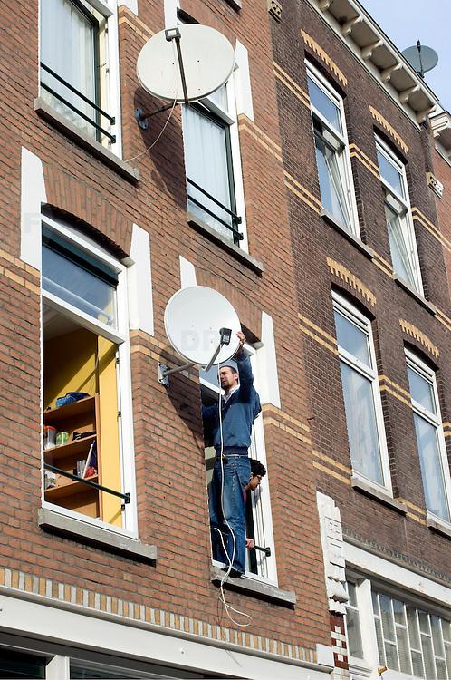 Nederland Rotterdam 10 oktober 2008 20081010 Foto: David Rozing ..Allochtone man, staand in raamkozijn,  installeert schotel antenne op de buitengevel op 1e verdieping in achterstandswijk Delfshaven..Foto David Rozing