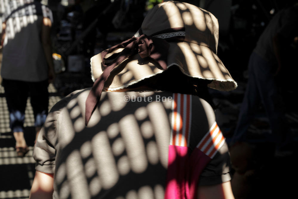 woman with large brim hat with sunlight pattern from grid above