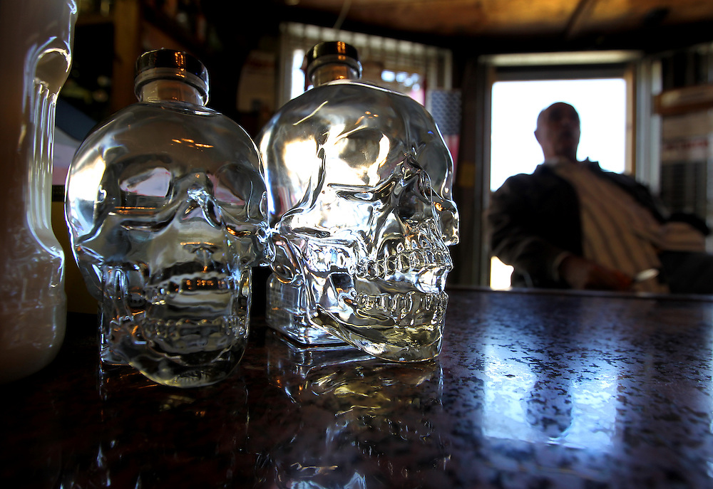 """Shawnee Liquor Store manager Dick Noble sits by the cash register in Fink, Texas, November 18, 2010.  The store is an old house that was built around 1910 and moved to Fink from Dennison.  Noble claims that the wine room has a """"spook""""."""