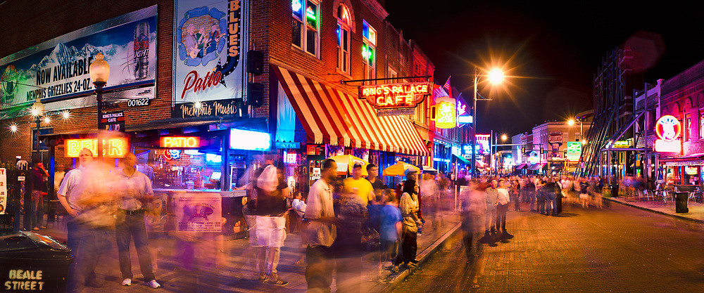 A lively scene of neon lights and crowds of people on a busy night along Beale Street. Memphis, TN