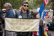 "A man holds a banner reading ""You can no longer sleep once you've opened your eyes."""