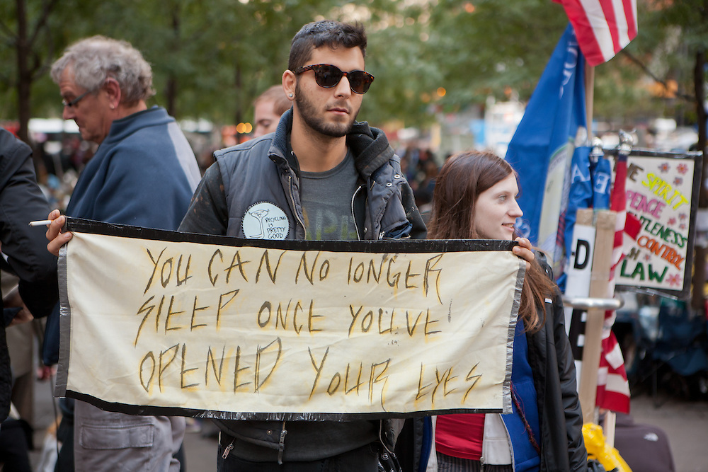 """A man holds a banner reading """"You can no longer sleep once you've opened your eyes."""""""
