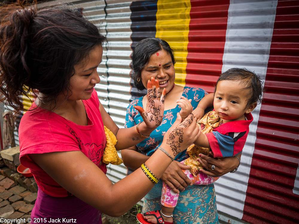 02 AUGUST 2015 - BHAKTAPUR, NEPAL:  Women with a baby in a small Internal Displaced Person (IDP) camp in Bhaktapur. Bhaktapur was badly damaged in the earthquake the hit Nepal in April 2015. The Nepal Earthquake on April 25, 2015, (also known as the Gorkha earthquake) killed more than 9,000 people and injured more than 23,000. It had a magnitude of 7.8. The epicenter was east of the district of Lamjung, and its hypocenter was at a depth of approximately 15km (9.3mi). It was the worst natural disaster to strike Nepal since the 1934 Nepal–Bihar earthquake. The earthquake triggered an avalanche on Mount Everest, killing at least 19. The earthquake also set off an avalanche in the Langtang valley, where 250 people were reported missing. Hundreds of thousands of people were made homeless with entire villages flattened across many districts of the country. Centuries-old buildings were destroyed at UNESCO World Heritage sites in the Kathmandu Valley, including some at the Kathmandu Durbar Square, the Patan Durbar Squar, the Bhaktapur Durbar Square, the Changu Narayan Temple and the Swayambhunath Stupa. Geophysicists and other experts had warned for decades that Nepal was vulnerable to a deadly earthquake, particularly because of its geology, urbanization, and architecture.      PHOTO BY JACK KURTZ