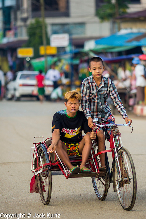 06 JUNE 2014 - IRRAWADDY DELTA,  AYEYARWADY REGION, MYANMAR: Boys on a pedicab in Pantanaw, a town in the Irrawaddy Delta (or Ayeyarwady Delta) in Myanmar. The region is Myanmar's largest rice producer, so its infrastructure of road transportation has been greatly developed during the 1990s and 2000s. Two thirds of the total arable land is under rice cultivation with a yield of about 2,000-2,500 kg per hectare. FIshing and aquaculture are also important economically. Because of the number of rivers and canals that crisscross the Delta, steamship service is widely available.   PHOTO BY JACK KURTZ