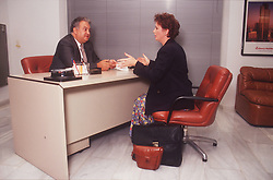 Business meeting between man and woman sitting across desk in office,
