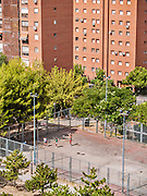 Madrid, August 2012. Urban scene, some friends playing basketball on a public field at a worker district.