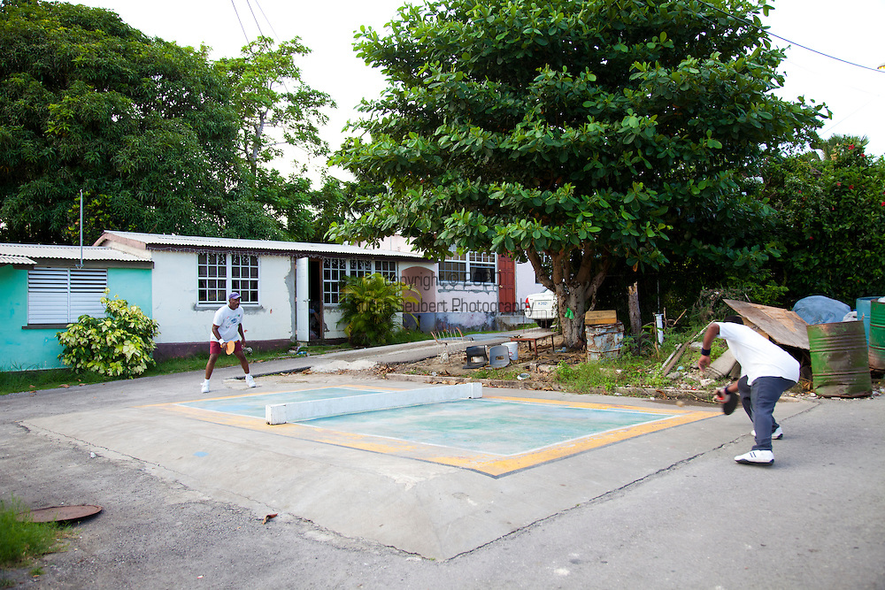 """Originating in Barbados in the 1930s, Road Tennis is played in on the back streets and roads of the country or now in permanent courts, such as the ones in Oistins and Speightstown.  The game is played on a 10x20 foot court and the """"net"""" is an 8 inch by 10 foot piece of wood.  It has the same rules as table tennis (ping pong) and is a 21 point game.  It uses hand hewn rackets made largely from plywood and tennis balls that have had the fur removed.  It is the only endemic sport to Barbados and is wildly popular among the local population.  Pictured here is a road tennis court in the back roads of the countryside."""