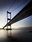 The Severn Bridge soars overhead in silhouette against sunrise light.