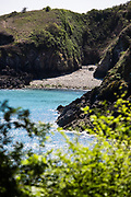 View through the trees of Vicard Harbour - a small hidden bay, only accessible by boat on the north coast of Jersey, Channel Islands