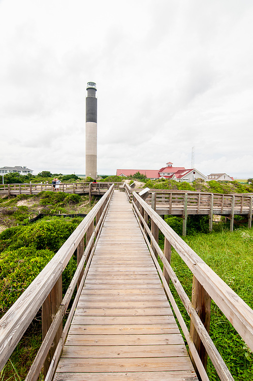 A wooden boardwalk connects the parking area, beach, and Oak Island Lighthouse in Oak Island, North Carolina on Saturday, August 7, 2021. Copyright 2021 Jason Barnette