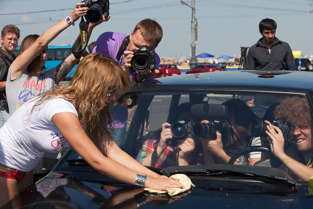"""Moscow Russia, 21/07/2011..A media scrum surrounds pro-Putin activists calling themselves """"We Love Putin"""" as they wash Russian-made cars in support of the domestic car industry. The young women in bikinis and high heel shoes say they can wash every Russian car for free to show their support for the Prime Minister, who is also known as a fan of Russian cars."""