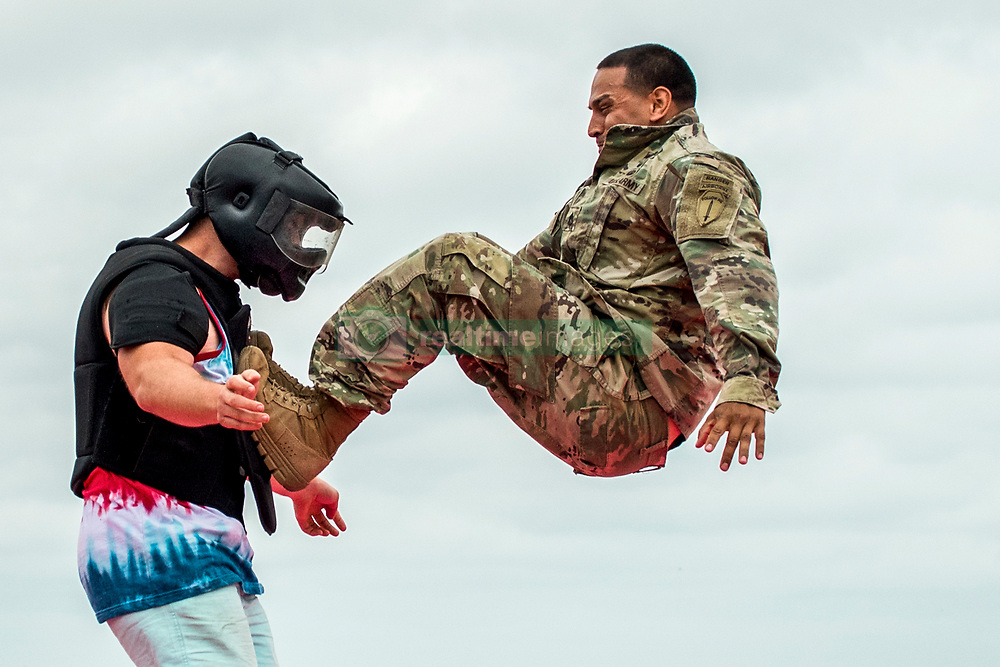"""A Soldier demonstrates hand-to-hand combat on a """"volunteer"""" from the crowd during the 6th Ranger Training Battalion's open house event April 29 at Eglin Air Force Base, Fla. The event was a chance for the public to learn how Rangers train and operate. The event displays showed equipment, weapons, a reptile zoo, face painting and weapon firing among others. The demonstrations showed off hand-to-hand combat, a parachute jump, snake show, and Rangers in action. (U.S. Air Force photo/Samuel King Jr.)"""