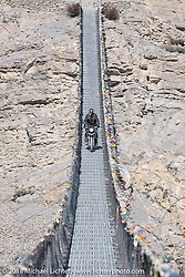 Round the World Doug Wothke rding across a narrow suspension bridge over the Kali Gandaki River on day-6 of our Himalayan Heroes adventure riding from Muktinath to Tatopani, Nepal. Sunday, November 11, 2018. Photography ©2018 Michael Lichter.