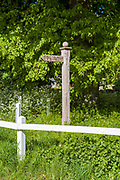 Wooden footpath sign directing walkers to a public footpath and white wooden fence rail in Swinbrook, the Cotswolds, Oxfordshire, UK
