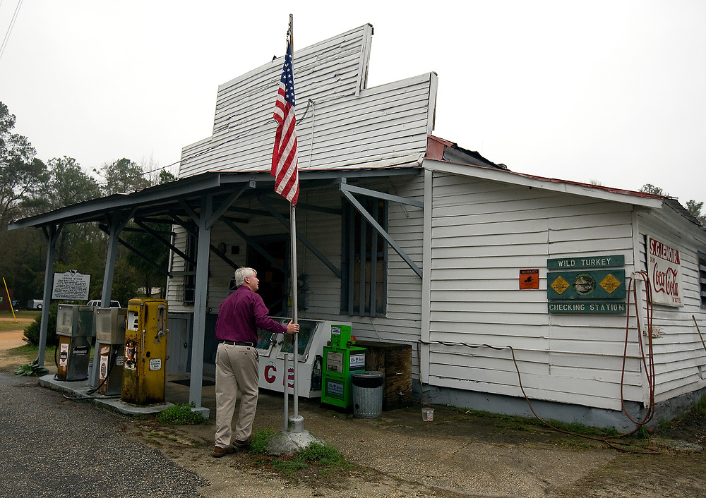 As part of his postmaster duty, Steve LeNoir raises the American flag outside of his families' general store.