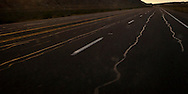 Painted converging lines mix with wavy long patches in the blacktop pavement of US 550 in rural NW New Mexico  panorama