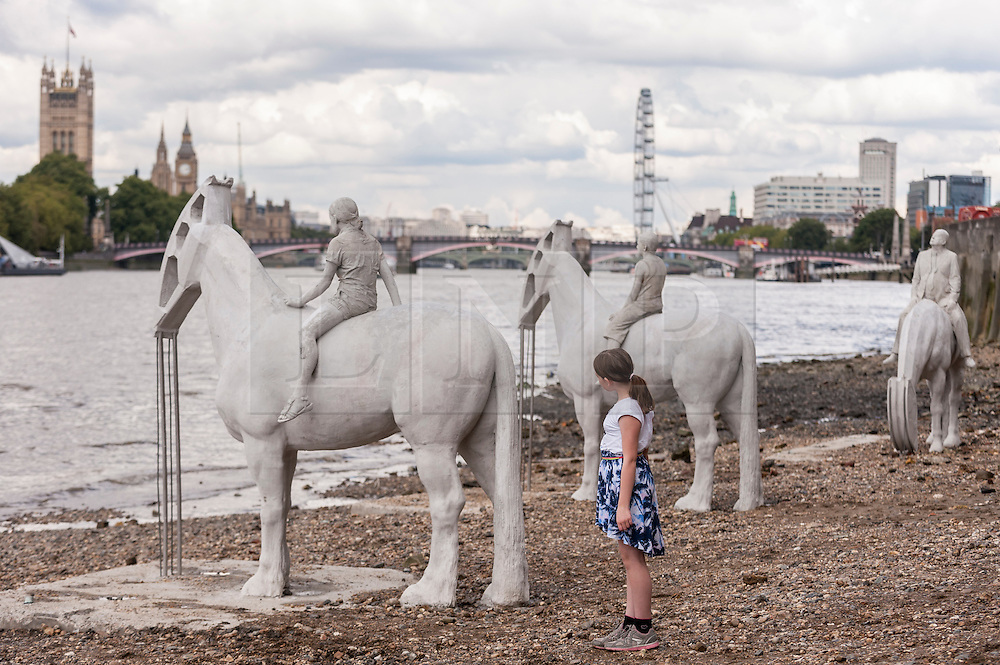 """© Licensed to London News Pictures. 02/09/2015 London, UK. A girl looks at the art installation entitled """"The Rising Tide"""" (comprising four horse-riders on horses with petroleum pumps for heads) by the underwater eco-sculptor Jason deCaires Taylor, which stands on the foreshore of the River Thames in Vauxhall and is revealed with each low tide.  The installation aims to question man's reliance on fossil fuels and is part of this year's Totally Thames festival. Photo credit : Stephen Chung/LNP"""