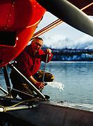 Pilot Howard Bowman pumping water from floats of his Stinson Voyager 198, Hardenburg Bay of Lake Clark, Port Alsworth, Alaska.