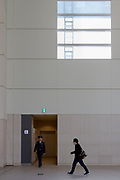 A Japanese man wearing a face mask walks passed a security guard under a window in Landmark Plaza at Landmark Tower, Minato Mirai, Sakuragicho, Yokohama, Japan. Saturday March 2nd 2019