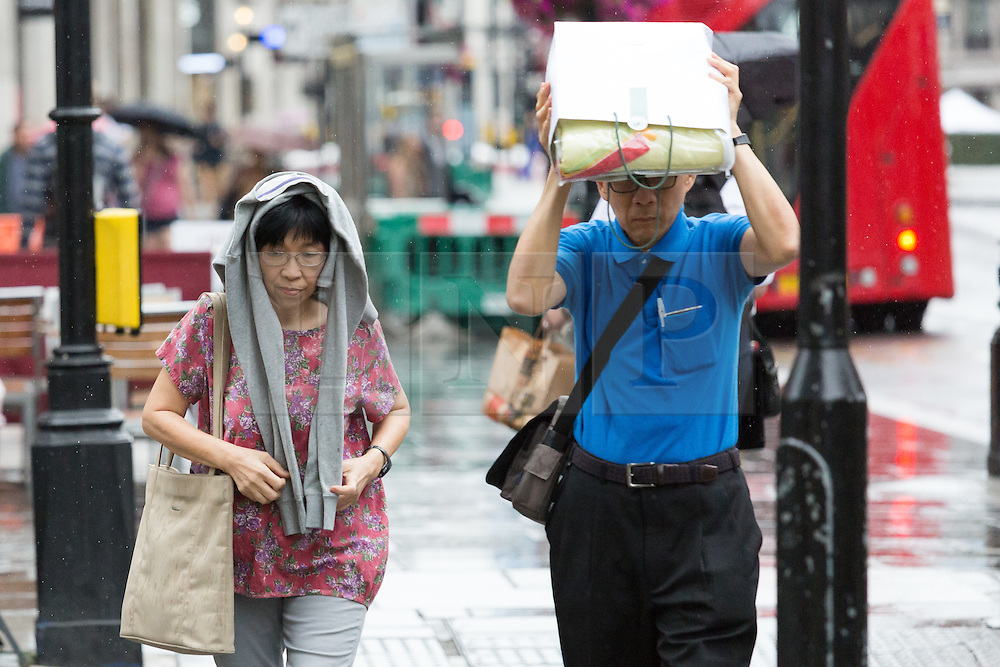 © Licensed to London News Pictures. 05/07/2015. London, UK. People shopping in Regent Street during rain showers and wet weather today. Photo credit : Vickie Flores/LNP