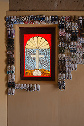 baby shoes hanging on a church wall with a stained glass window of a cross