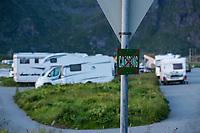 Tourist motorhomes ignoring 'No Camping' sign and camping illegally at popular beach of Skagsanden, Flakstadøy, Lofoten Islands, Norway
