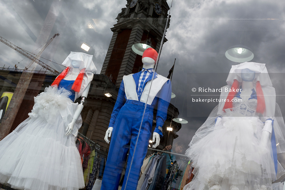 With the reflection of Lambeth Town Hall are three shop mannequins dressed in red, white and blue coloured clothing, stand in the window of second-hand clothes retailer Traid, on 4th July 2017, in Brixton, London, England.