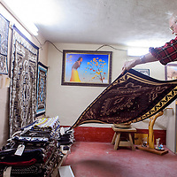 Two Grey Hills trading post owner Les Wilson lays a rug out in the store's rug room Tuesday. Wilson says the weaving and popularity of Two Grey Hills style rugs is what keeps business going.
