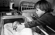 """A two and half year-old girl meets her sleeping baby brother for the first time on his actual birthday. In the maternity ward at Kings College Hospital, Camberwell, London, the child reaches out with the maternal instincts of her gender to touch the fragile infant who is wrapped up in an NHS blanket in a cot that was wheeled directly from the birthing room a few hours beforehand. The baby boy is oblivious to his sister's affection and attention but he is healthy and already thriving before waking up for his first feeds. From a personal documentary project entitled """"Next of Kin"""" about the photographer's two children's early years spent in parallel universes."""