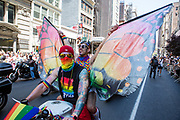New York, NY - 30 June 2019. The New York City Heritage of Pride March filled Fifth Avenue for hours with participants from the LGBTQ community and it's supporters. Motorcyclists led the march, and included this tattooed driver and  his companion, who waved large butterfly wings.
