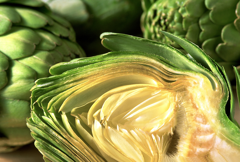 Close up selective focus photograph of three Artichokes on a table