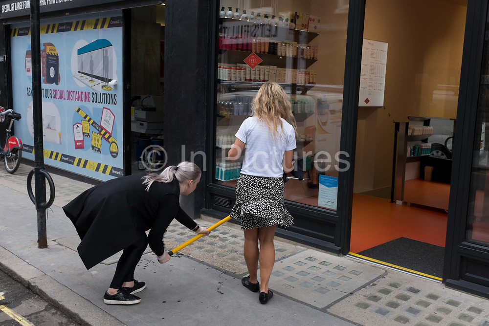 With a further 89 UK covid victims in the last 24hrs, bringing the total victims to 43,995 during the Coronavirus pandemic, pubs, restaurants and hairdressers will be able to reopen on 4th July, providing they adhere to COVID Secure guidelines. Sandra, owner of Feel Hairdressers Soho, is helped by friend, Brigitte, to re-open the business by cleaning the front windows, on Berwick Street in Soho, on 2nd July 2020, in London, England.