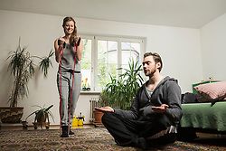 Couple doing exercise in living room, Munich, Bavaria, Germany