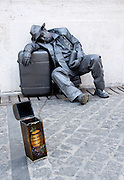 A performance artist poses as a bronze statue with his tip box chained to himself.
